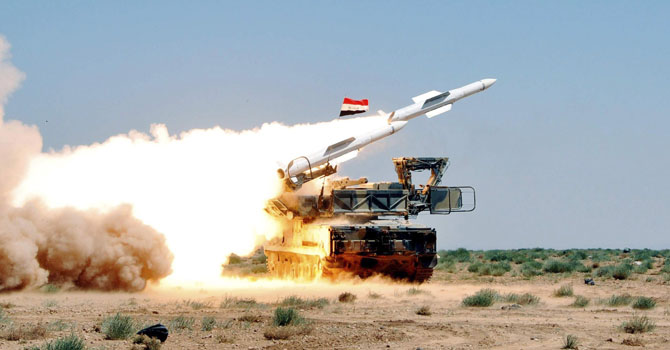 A missile is launched from a mobile platform during a live ammunitions exercise by Syrian air defence forces in an undisclosed location.